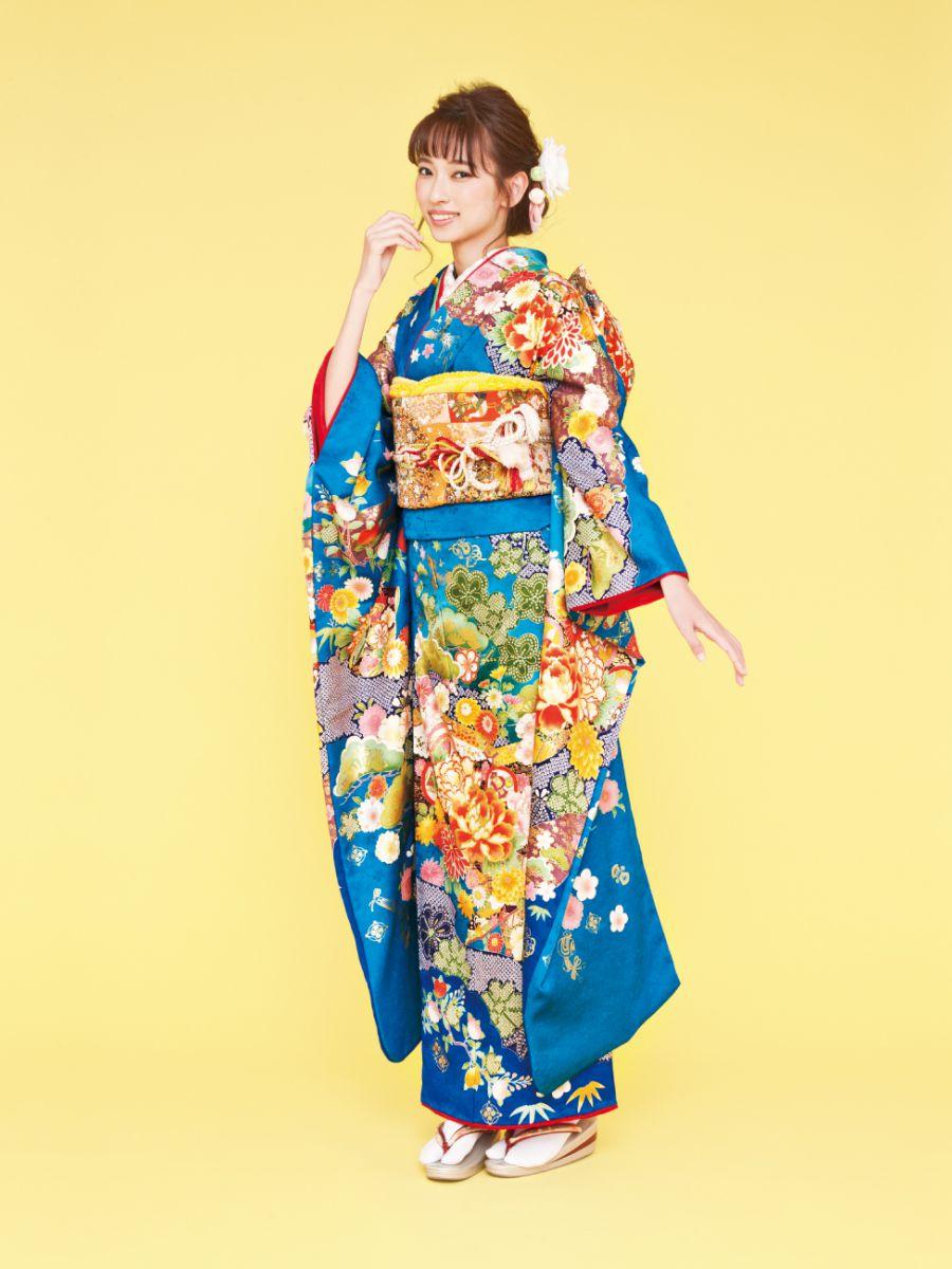 振袖コレクションNO:K217/パッと目を引く様な、鮮やかなブルー色。ボタンや松など古典柄を美しい色合いで表現。帯や襟元は地色のブルーを引き立たせるように橙色を。あなたらしいコーディネートで着飾ってみて。