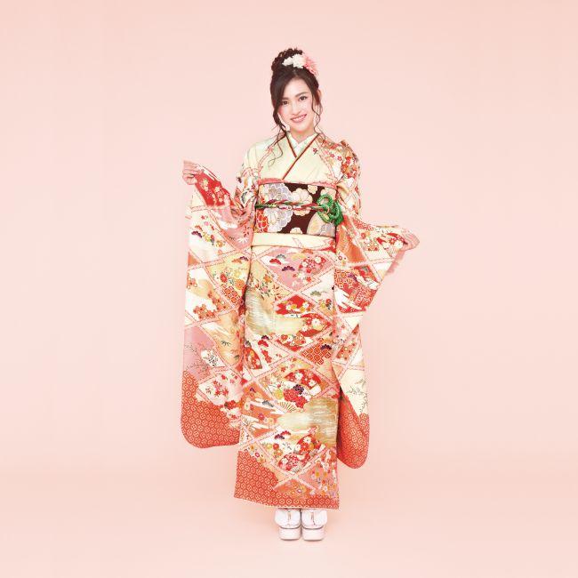 振袖 N103:花々の風情が持つ詩のような美しさを文様化した上品な一着。光沢のある綸子地に描かれた松皮菱と扇、四季の花が個性的。やわらかな色合いで優しい雰囲気。